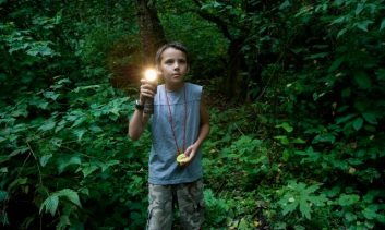Boy with torch in forest --- Image by © Image Source/Corbis